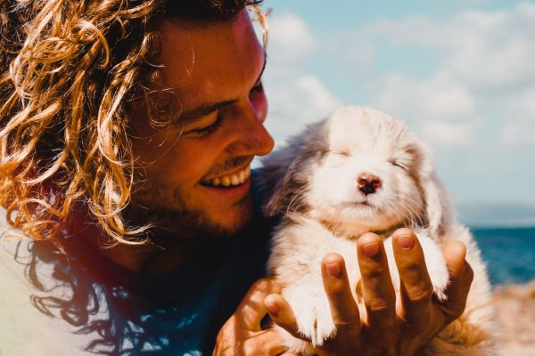 Man with long hair in blue shirt holding sleeping puppy on beach